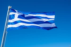 Greek flag waving against blue sky background.